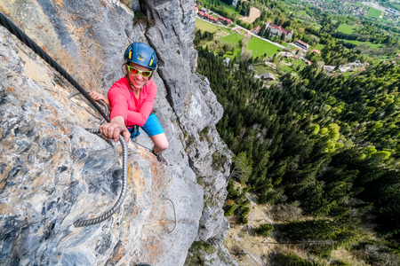 via: Young woman climber having fun during via ferrata ascent