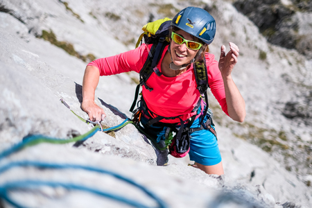Young woman having fun during rock climbing ascent