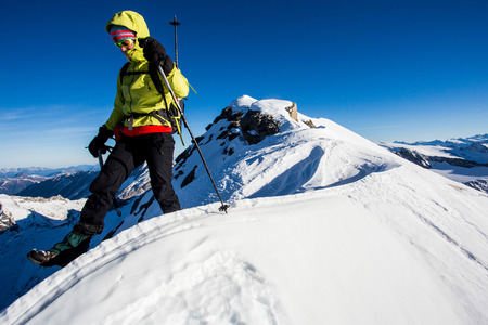 snow climbing: Young woman climbing challenging snow ridge in the Alps