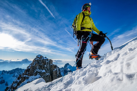 Young woman climbing snow ridge Stock Photo