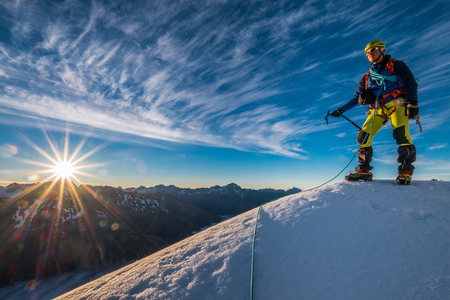 Mountaineer with ice-axe enjoying the sunrise in the Alps Stock Photo