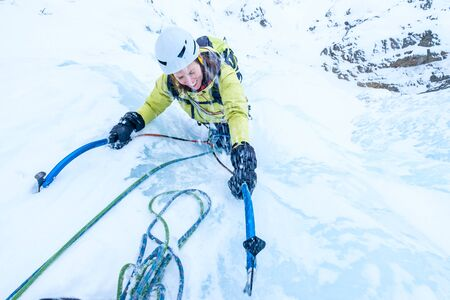 Young woman climbing the icefall