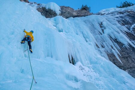Young climber climbing blue icefall