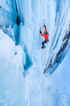 Climber scaling the huge icefall in the Dolomites Фото со стока