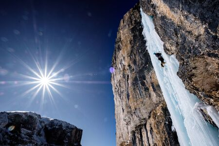 Climber leading the icefall under full sun