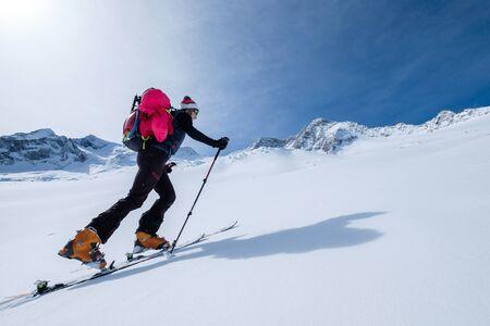 Mujer joven en esquís subiendo la ladera de la montaña