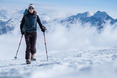 Junge Frau auf Skiern, die den Berghang besteigen