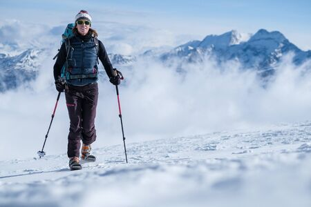 Young woman on skis ascending the mountain slope