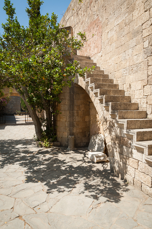 Stone volute, top part of Ionic column. Stone stairs build on arch masonry. Tree giving a shade. Stock fotó
