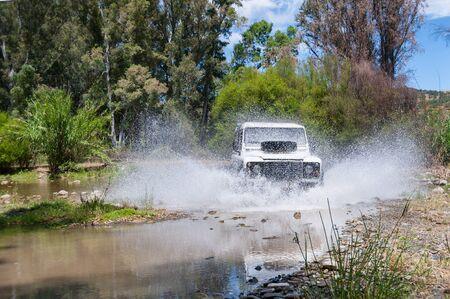 Rural Andalucia. Spain. 06102016. Riverbed crossing in 4x4 terrain vehicle on speed with water splashing. 版權商用圖片
