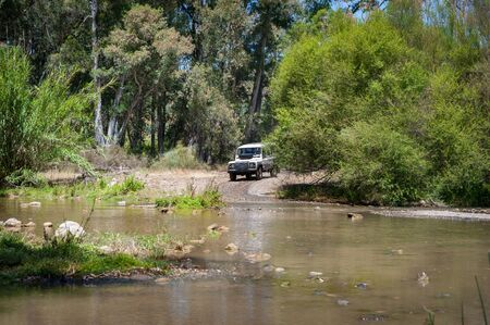 Rural Andalucia. Spain. 06102016. 4x4 terrain vehicle approaching river in order to drive across.