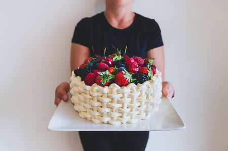 Woman holding plate with beautiful summer cake decorated with berries against white wall background.