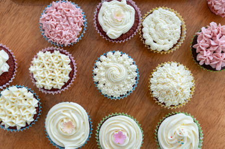 Home baked cupcakes beautifully decorated with buttercream on top placed on wooden table.