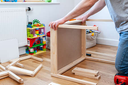 A male adult person assembling flom flat-pack a set of two small chairs with desk in child's bedroom.