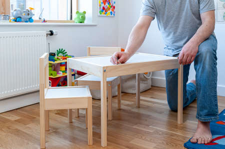 A parent assembling from flat pack a set of two small chairs with desk in childs bedroom. Archivio Fotografico
