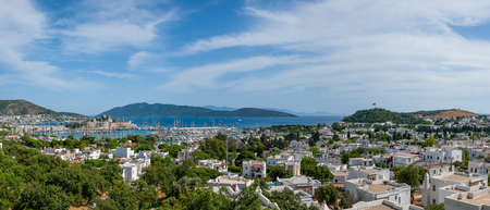 Panoramic distant view at Bodrum town with Limaru harbor. Yachts and sail boats anchored in calm waters of Bodrum shallow moon-shaped bay in Turkey.