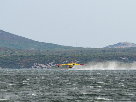 aerial bomb: Firefighter airplane, water bomber, air tank taking water from the sea and extinguishing forest fire in Croatia, close to Krka national park and Skradin town, Sibenik region
