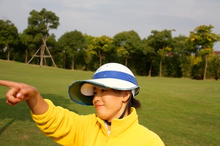 caddie: Golf caddie of China point to where the golf ball went Stock Photo