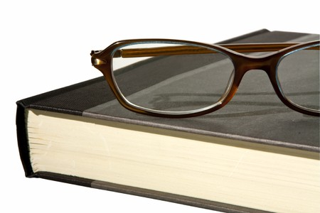 hardback: a close up partial view of a hardback book with a pair of reading glasses on top