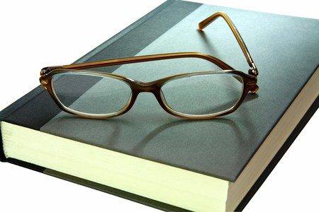 hard back book with pair of reading glasses on top close up