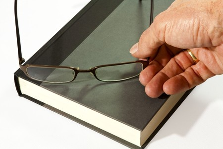 hardback: hardback book with a mans hand putting his reading glasses on the book Stock Photo