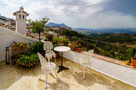 Título: terrace with white chairs and table with landscape in the background