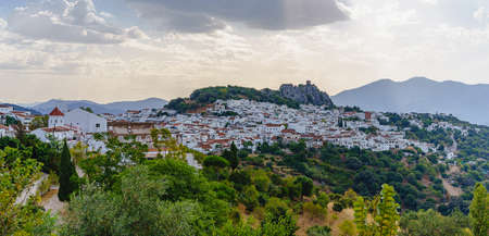 white spanish village landscape panoramic view with green bushes and cloudy sky