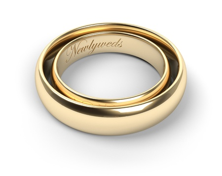 Gold wedding rings engraved with the text Newlyweds photo