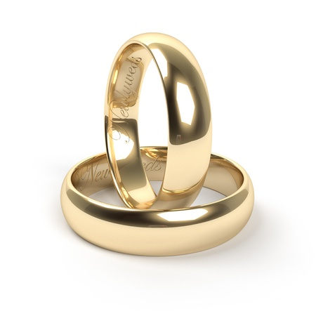 verlobung: Goldene Trauringe mit dem Text Newlyweds eingraviert