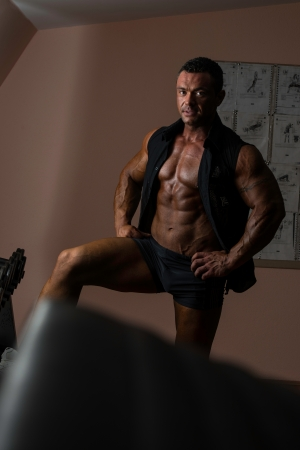 physique: male bodybuilder posing in black shirt without sleeves