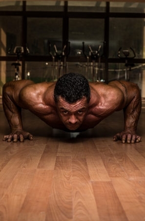 male bodybuilder doing push ups at the floor photo