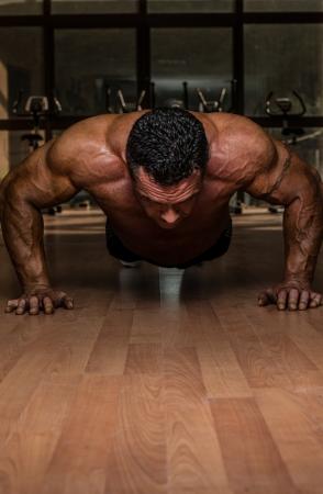 männliche Bodybuilder tun Push-ups auf dem Boden