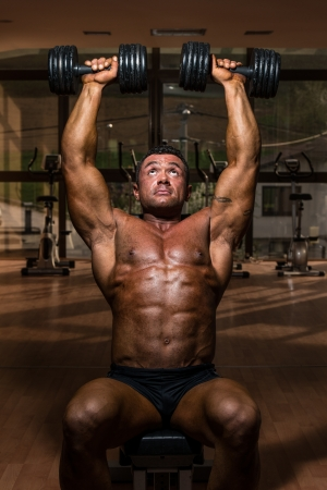 male bodybuilder doing shoulder press whit dumbbell photo