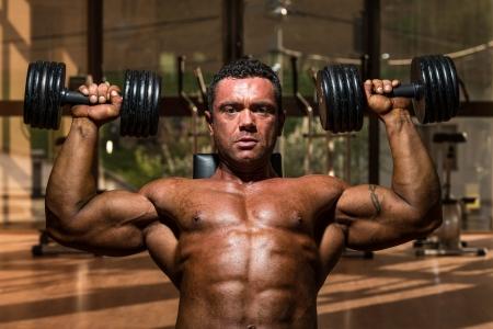 male bodybuilder doing shoulder press whit dumbbell photo