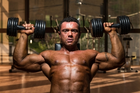 muscular body: male bodybuilder doing shoulder press whit dumbbell