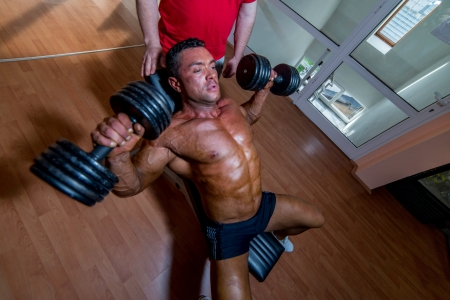 body builder: training in gym where partner gives encouragement