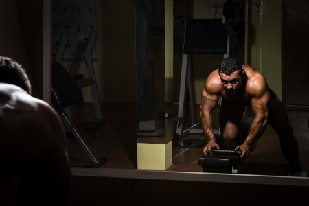male bodybuilder doing heavy weight exercise for back photo