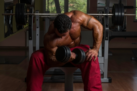 body builder: shirtless bodybuilder doing heavy weight exercise for biceps Stock Photo
