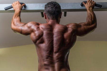 male body builder doing heavy weight exercise for back photo