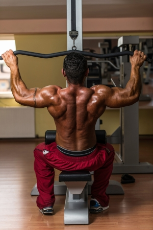 shirtless bodybuilder doing heavy weight exercise for back photo