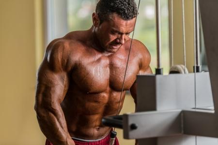 hombres haciendo ejercicio: culturista haciendo ejercicios de peso pesado para tríceps con cable Foto de archivo