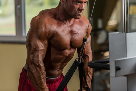 body building: bodybuilder doing heavy weight exercise for triceps with cable