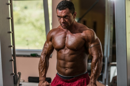 male bodybuilder doing heavy weight exercise for trap photo