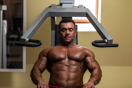 bodybuilder resting after doing heavy weight exercise photo