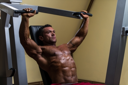 male bodybuilder doing heavy weight exercise for upper chest photo