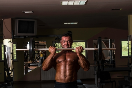 bodybuilder doing heavy weight exercise for biceps with barbell photo