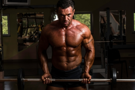 body building: bodybuilder doing heavy weight exercise for biceps with barbell