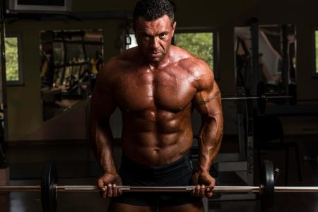 Bodybuilder tun schwere Übung für Bizeps mit Langhantel