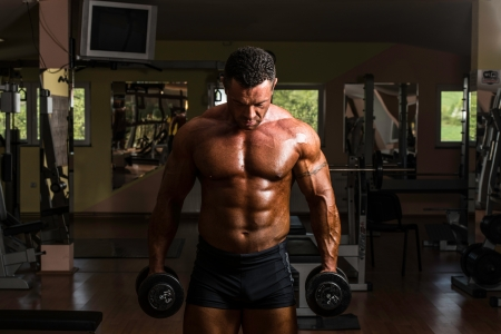 bodybuilder doing heavy weight exercise for biceps with dumbbell photo