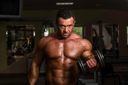 physique: bodybuilder doing heavy weight exercise for biceps with dumbbell Stock Photo